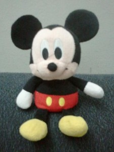 Baby Mickey Mouse perched on top of couch